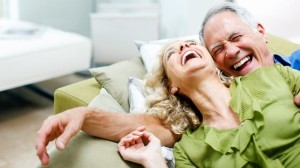 A picture of a male and female laughing on a couch